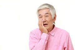 Den höga japanska mannen lider från tandvärk Arkivfoto