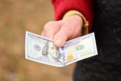 Den höga kvinnan är hållande pengar i hennes hand Pengar i gammal kvinnas hand Arkivbilder