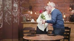 Den höga kvinnan ankommer på ett datum, och hennes partner ger hennes blommor arkivfilmer