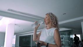 Den höga kvinnan dricker upp vatten från dricksvatten i idrottshallen, slut stock video
