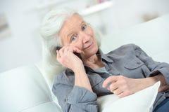 Den höga kvinnan har lycklig konversation på telefonen arkivbild