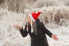 Den höga kvinnan i den roliga santa hatten med råttsvansar som visar den öppna handen, gömma i handflatan för produkt eller text Royaltyfri Foto