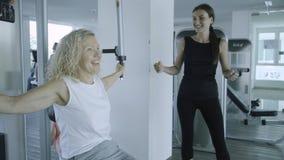 Den höga kvinnan kopplas in på en simulator i idrottshallen med en personlig instruktör dottern hjälper mamman i idrottshallen arkivfoton