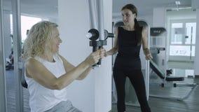 Den höga kvinnan kopplas in på en simulator i idrottshallen med en personlig instruktör dottern hjälper mamman i idrottshallen royaltyfria bilder