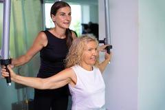Den höga kvinnan kopplas in på en simulator i idrottshallen med en personlig instruktör dottern hjälper mamman i idrottshallen royaltyfri foto