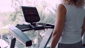 Den höga kvinnan kopplas in på en trampkvarn i idrottshallen mot bakgrunden av det panorama- fönstret lager videofilmer