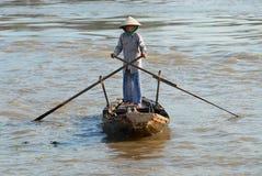 Den höga kvinnan korsar Mekong River vid en traditionell träpaddleboat i Cai Be, Vietnam Royaltyfri Bild