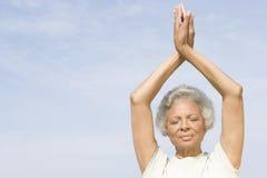 Den höga kvinnan med ögon som stängs i yoga, poserar royaltyfria bilder