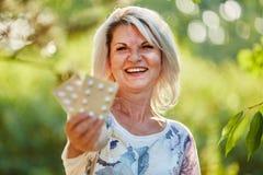 Den höga kvinnan med medicin skrattar lyckligt royaltyfri bild