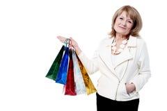 Den höga kvinnan med shopping hänger lös Arkivbild