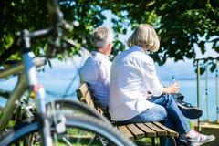 Den höga kvinnan och mannen på vilar på cykeltur fotografering för bildbyråer