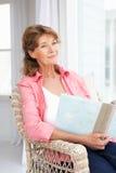 Den höga kvinnan satt med fotoalbum Arkivfoton