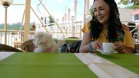 Den höga kvinnan sitter med hennes förtjusande husdjur - den vita hundpekinesen i ett utomhus- kafé för sommar stock video