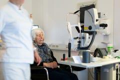 Den höga kvinnan som beeing, prepered för laser-kirurgi på oftalmologikliniken Arkivbild