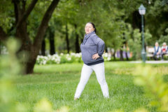 Den höga kvinnan som gör sporten parkerar in Fotografering för Bildbyråer