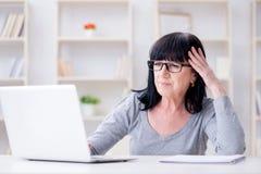 Den höga kvinnan som kämpar på datoren arkivbild