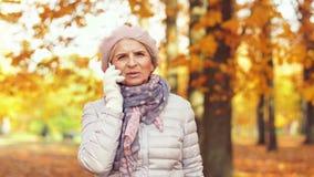 Den höga kvinnan som kallar på smartphonen på hösten, parkerar lager videofilmer