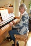 Den höga kvinnan spelar pianot arkivfoton