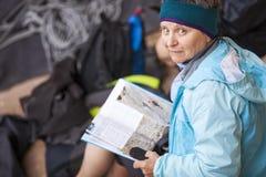 Den höga kvinnan vaggar den hållande resehandboken för klättraren Arkivfoto