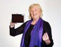 Den höga kvinnan visar tabletdatoren Royaltyfri Fotografi
