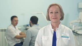 Den höga kvinnliga doktorn som ser kameran, medan manligt, manipulerar samtal till patienten på bakgrunden arkivfilmer