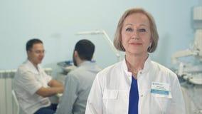 Den höga kvinnliga doktorn som ser kameran, medan manligt, manipulerar samtal till patienten på bakgrunden Royaltyfri Fotografi