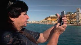 Den höga kvinnliga lyckliga vuxna turisten på ett fartyg använder en mobil smartphonekamera för att få panorama- foto av en tropi arkivfilmer