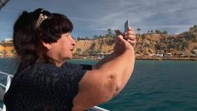 Den höga kvinnliga lyckliga vuxna turisten på ett fartyg använder en mobil smartphonekamera för att fånga panorama- foto av ett t stock video