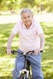 Den höga latinamerikanska mannen som in cyklar, parkerar Arkivbild