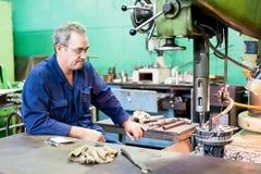 Den höga malningmaskinoperatören arbetar på maskinen Arkivbild
