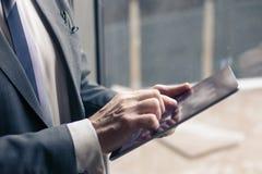 Den höga manliga arbetaren använder en touchpad royaltyfri foto