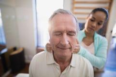 Den höga manliga patienten med ögon stängde hälerihalsmassage från kvinnlig terapeut royaltyfri bild