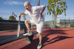 Den höga manliga tennisspelaren med tillbaka smärtar på domstolen Arkivfoto