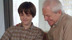 Den höga mannen hjälper hans sonson att montera leksakmedlet arkivfoto