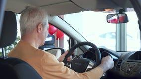 Den höga mannen justerar backspegeln inom bilen stock video