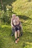 Den höga mannen kopplar av i rullstolen Arkivfoton