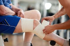 Den höga mannen med förbinder på benet efter skada i idrottshall arkivbilder