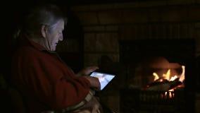 Den höga mannen sitter på spisen med minnestavlan och hållande ögonen på familjvideo lager videofilmer