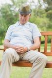 Den höga mannen som sover på bänk på, parkerar Royaltyfria Bilder