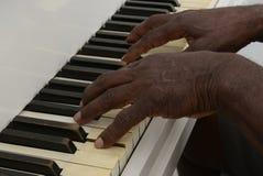 Den höga mannen spelar pianot Arkivfoton