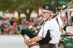 Den höga mannen spelar säckpipa, för den gamla soldatdagen ståtar Royaltyfri Fotografi