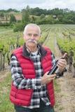 Den höga mannen stod av vinrankor som rymmer flaskvin Royaltyfria Bilder