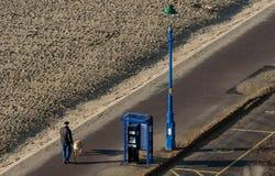 Den höga mannen tar hans hund för för att promenera den sandiga stranden på en härlig solig dag arkivfoton