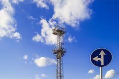 Den höga masten eller polen med strålkastare och ett trafiktecken 'går den raka eller vänstra vänden 'mot en blå himmel med vita  royaltyfria bilder
