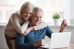 Den höga mitt åldrades lyckliga par som omfamnar genom att använda bärbara datorn tillsammans arkivfoton