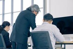 Den höga personalen i dräkt beställer mananställd för att beskåda en comput royaltyfria bilder
