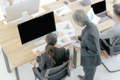 Den höga personalen i en dräkt beställer kvinnlig anställd för att beskåda com arkivfoton