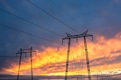 Den höga spänningspolen står högt brinnande himmelsolnedgångbakgrund royaltyfri foto