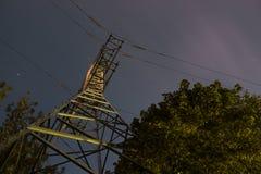 Den höga spänningsstolpen eller tornet beskådar upp med trädet, och natthimmel fördunklar Långt exponeringsfotografi Arkivfoton