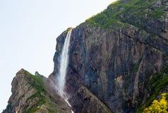 Den höga vattenfallet som flödar från branta klippor vaggar på Arkivfoton